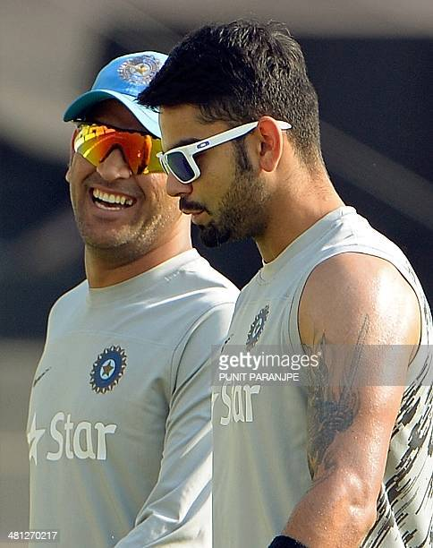 Indian captain Mahendra Singh Dhoni speaks with teammate Virat Kohli as they arrive for a training session at The ShereBangla National Cricket...