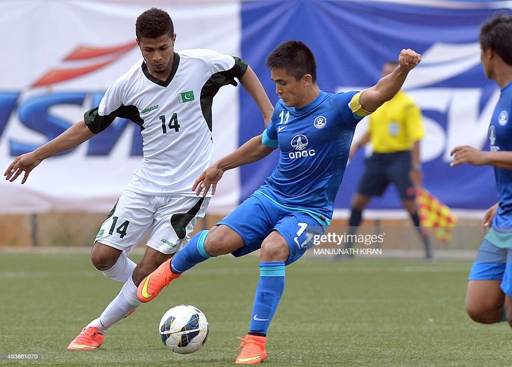 Indian captain Sunil Chhetri (R) tussles with Pakistani player Sher Muhammad Baloch (L) during their second friendly football match in Bangalore at the Karnataka State Football Association Stadium in Bangalore on August 20, 2014. Pakistan pulled off a surprise 2-0 win over India, with a late goal from Saddam Hussain ensuring a share of the spoils for the visitors in the first football series between the arch rivals for a decade. AFP PHOTO/Manjunath KIRAN