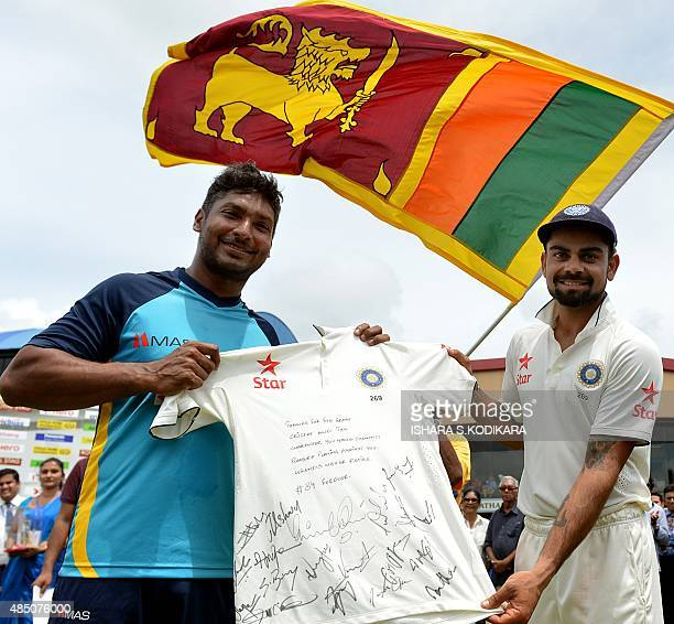 Indian captain Virat Kohli hands over a tshirt signed by the Indian cricketers to Sri Lankan cricketer Kumar Sangakkara at close of play on the fifth...