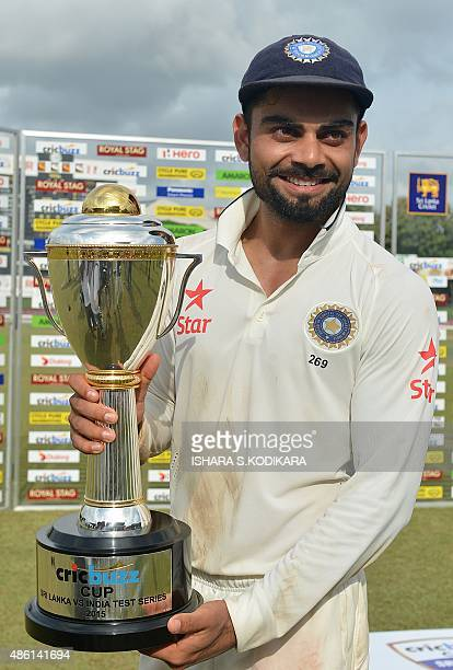 Indian captain Virat Kohli smiles as he holds the trophy after his team's victory during the final day of the third and final Test match between Sri...