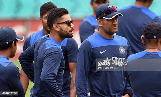 Indian captain Virat Kohli speaks to teammates as former captain Mahendra Singh Dhoni listens during a cricket training at the Sydney Cricket Ground...