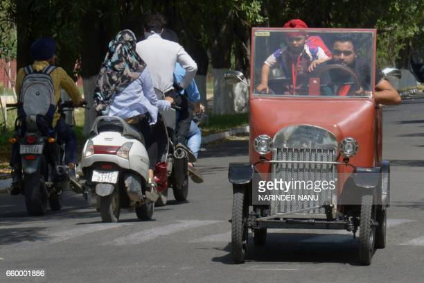 Indian car enthusiast Kiranjot Singh Bhullar drives his son in a car assembled using a range of TFord1925 model parts and run on a batteryoperated...
