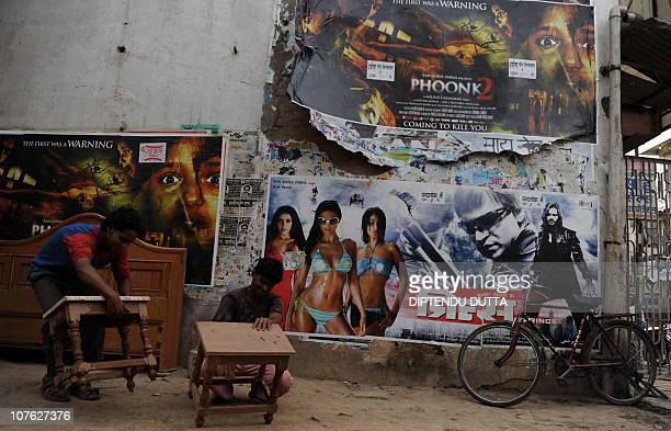 Indian carpenters works below Indian movie advertisement posters pasted in layers onto a building in Allahabad on April 20 2010 India with its 12...