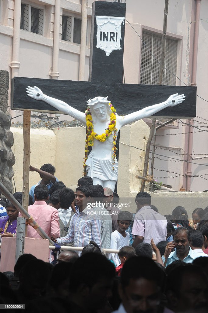 Indian Catholic christians offer prayers at the statue of a crucified Jesus Christ at the Shrine of Our Lady of Health in Hyderabad on September 8, 2013. The Catholic community celebrated the annual Feast of the Birth of Mother Mary. AFP PHOTO / Noah SEELAM