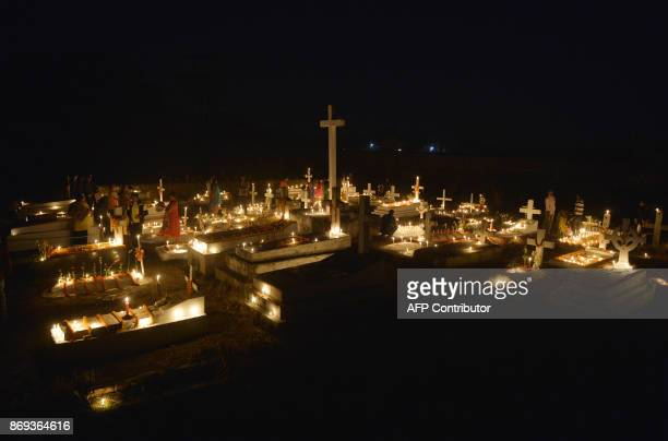Indian Catholic devotees light candles at the graves of their relatives during All Souls Day in Siliguri on November 2 2017 All Souls Day is observed...