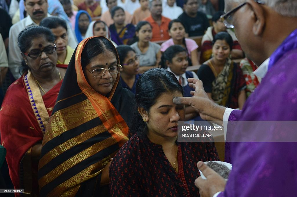 Indian Catholic Priest marks the symbol of the cross with ash on the forehead of a young Christian devotee during an Ash Wednesday service at Saint Mary's Basilica in Secunderabad, the twin city of Hyderabad, on February 10, 2016. Catholics began the 40 day Lenten season, by observing Ash Wednesday, which culminates in the Holy Week. AFP PHOTO / Noah SEELAM / AFP / NOAH SEELAM