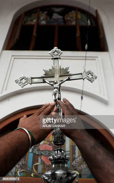 Indian Catholics reach towards a cross as they take part with others in a procession to reenact the crucifixion of Jesus Christ on the occasion of...
