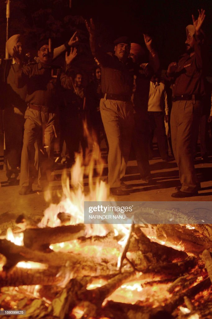 Indian Central Reserve Police Force (CRPF) 13th Battalion personnel dance around a fire as they celebrate the winter festival of Lohri in Amritsar on January 13, 2013. Lohri celebrates fertility, and people gather round the bonfires, throw sweets, puffed rice and popcorn into bonfires, sing popular songs, fly kites and exchange greetings. AFP PHOTO/ NARINDER NANU