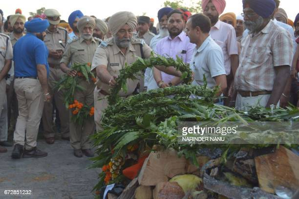 Indian Central Reserve Police Force officers lay wreaths on the pyre of CRPF personnel Raghbir Singh at his funeral in Sathiala village some 45km...