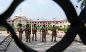 Indian Central Reserve Police Force personnel standing guard at the Allahabad High Court are seen through its closed gate during a strike by...