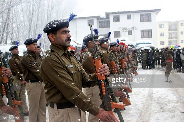 Indian Central Reserve Police Force soldiers stand amid heavy snowfall at a flag raising ceremony during Republic Day celebrations in Sopore area of...