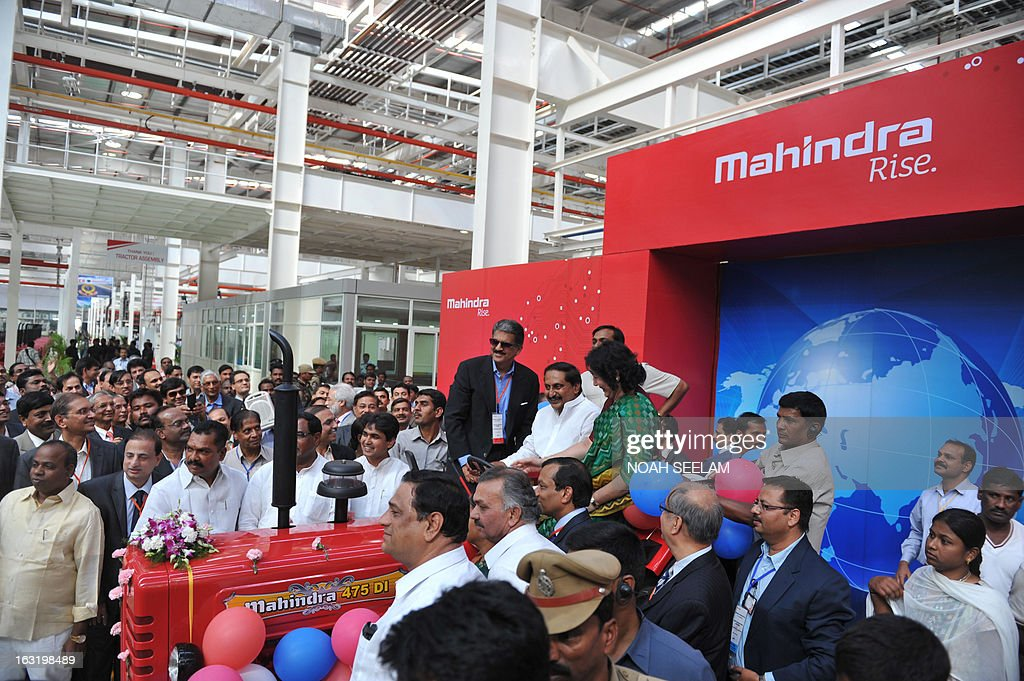 Indian Chairman and Managing Director, Mahindra and Mahindra (MM), Anand Mahindra(top L), Chief Minister of Andhra Pradesh, N.Kiran Kumar Reddy(top C), Minister for Major Industries in Andhra Pradesh, J Geeta Reddy(top R) sit on the newly launched Mahindra tractor at the opening of new manufacturing plant at Zaheerabad in Medak District, around 126 kilometres from Hyderabad on March 6, 2013. Auto-maker Mahindra Mahindra reported 10.99 percent increase in its total sales to 47,824 units in February 2013. The company sold 43,087 units in the same month in 2012, MM said in a statement. AFP PHOTO / Noah SEELAM