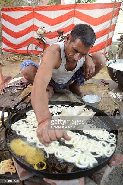 Indian chef Bhagat Kumar prepares the sweet 'Jalebi ' in Amritsar on October 24 2012 Jalebi are in huge demand during the Hindu festival of Dussehra...
