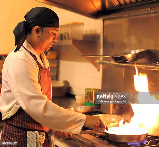 Indian chef cooking over flaming pan