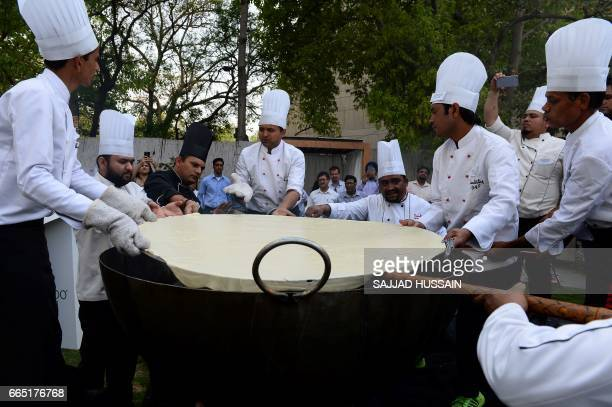 Indian chefs prepare a bhatura a fried bread during an attempt to make India's largest bhatura in New Delhi on April 6 2017 The bhatura measures 147...