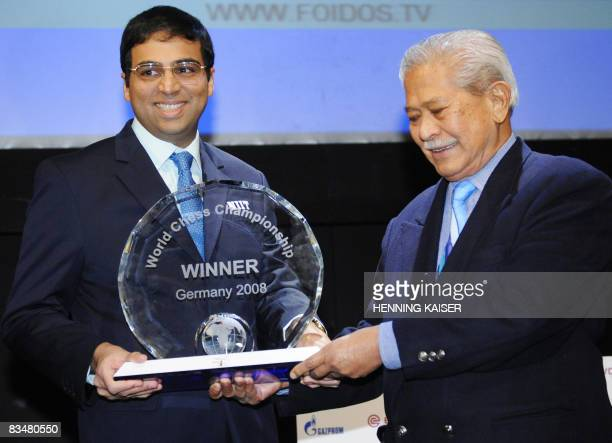 Indian chess world champion Viswanathan Anand receices the trophy from FIDE World Chess Federation president Kirsan Iljumzhinov after winning the...