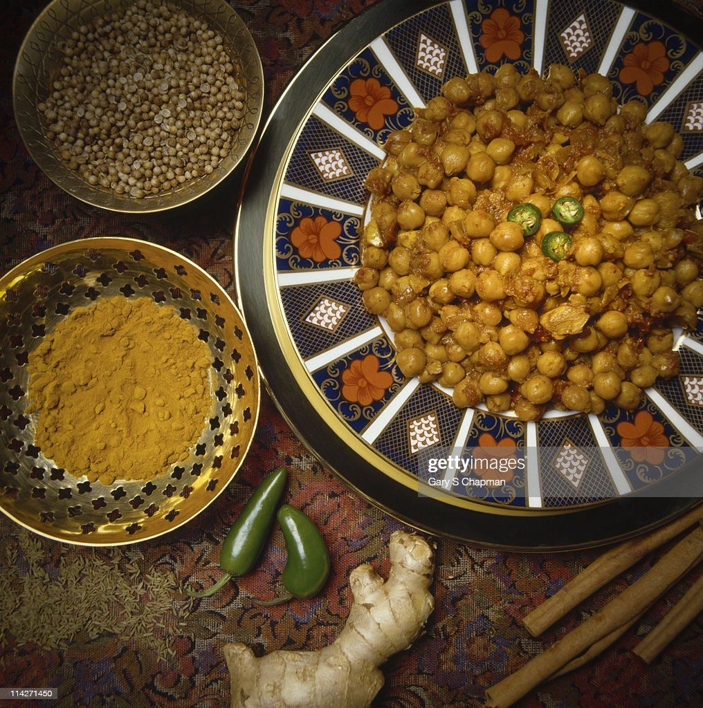 Indian chickpea curry dish and raw spices : Stock Photo