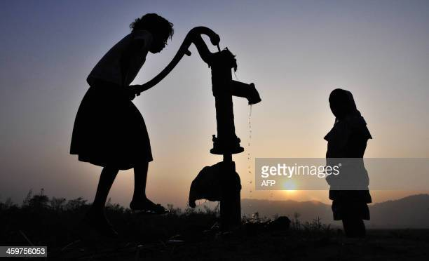 Indian children collect drinking water from a tubewell in the village of Murkata in Morigoan district some 70 kms from Guwahati on December 30 2013...