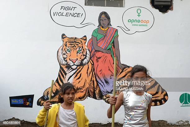 Indian children dance in front of a mural depicting fictional character Priya who is a rape survivor sitting on a tiger before a march starts in New...