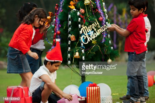 People Decorating A Christmas Tree indian boy decorating christmas tree stock photo | getty images