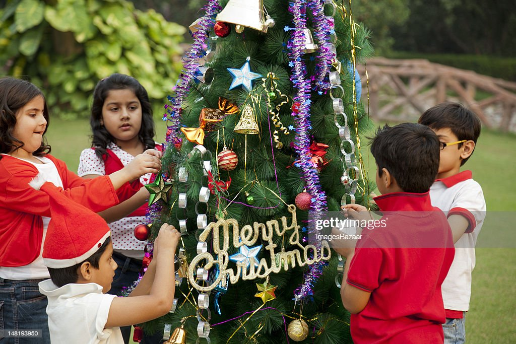 indian children 6 8 decorating christmas tree stock photo - People Decorating A Christmas Tree