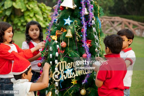 People Decorating For Christmas indian children decorating christmas tree stock photo | getty images