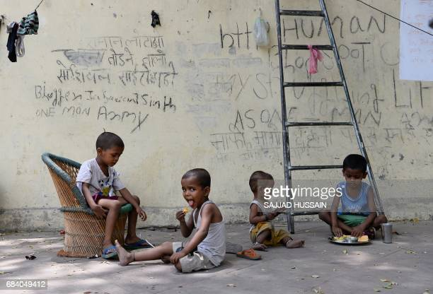 TOPSHOT Indian children eat food on a foothpath in New Delhi on May 17 2017 / AFP PHOTO / SAJJAD HUSSAIN