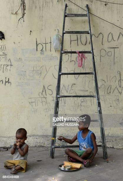 Indian children eat food on a foothpath in New Delhi on May 17 2017 / AFP PHOTO / SAJJAD HUSSAIN