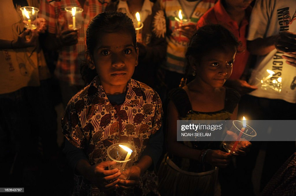 Indian children hold candles as demonstrators take part in a candlelight vigil to pay tribute to victims who died in recent twin blast in Hyderabad on February 25, 2013. Indian Prime Minister Manmohan Singh on February 24 appealed for calm as he flew to Hyderabad and visited some of the 117 people wounded in twin bombings last week which killed 16 people. AFP PHOTO / Noah SEELAM