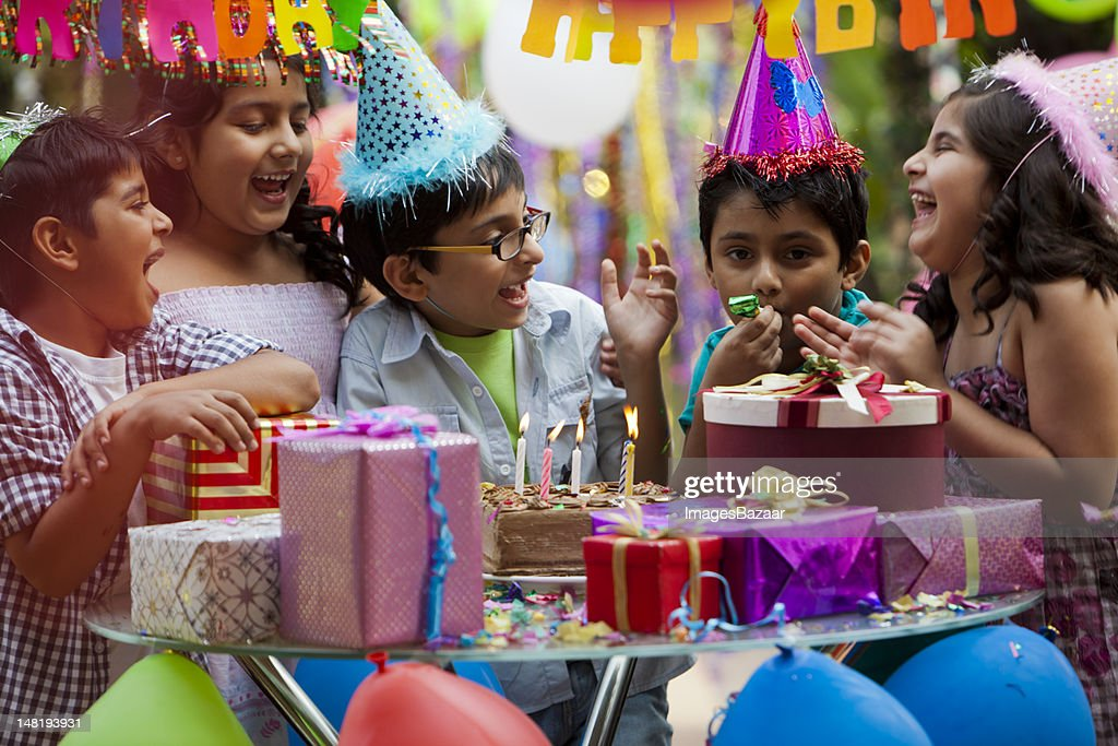 Indian children (6-8) laughing during birthday party : Stock Photo