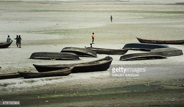 Indian children of boatmen play in a dry river bed area as the water level of Ganga recedes due to extreme hot weather and short water supply from...
