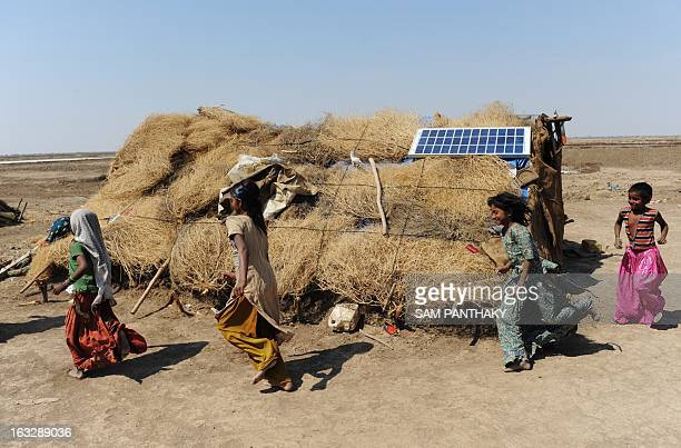 Indian children of salt workers play near a makeshift dwelling on the eve of International Women's Day in the Santalpur region of Little Rann of...