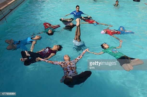 Indian children perform water yoga as they take part in a mass yoga session to mark the International Yoga Day at Dau ri Dhani Swiming Pool in...