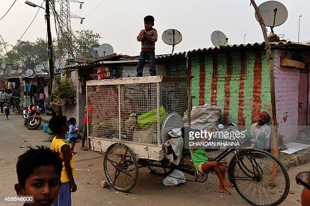 Indian children play along a back alley in a slum colony in New Delhi on November 12 2014 India is part of a global trend that is advancing towards...
