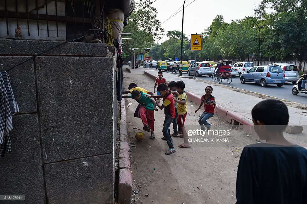 Indian children play football near their home in the slums of New Delhi on June 28, 2016. / AFP / Chandan KHANNA
