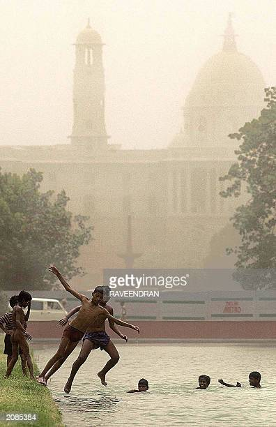 Indian children play in a fountain in front of government buildings engulfed by a dust storm in New Delhi 06 June 2003 India's capital received some...