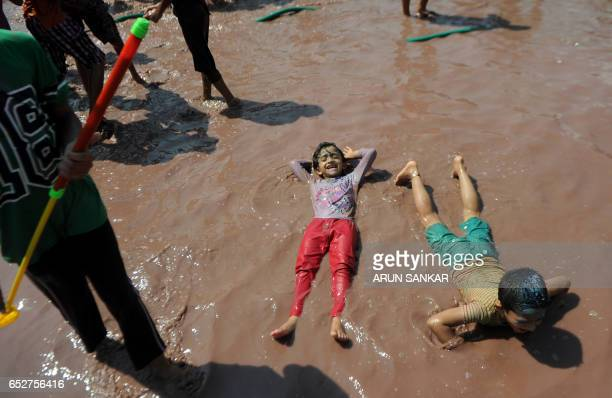 Indian children play in pools of coloured water during Holi celebrations in Chennai on March 13 2017 The Hindu festival of Holi or the 'Festival of...