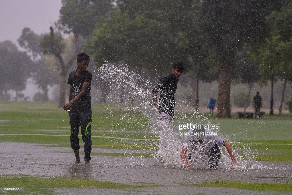 Indian children play in puddles of rainwater after heavy monsoon showers struck New Delhi on June 30, 2016. / AFP / CHANDAN