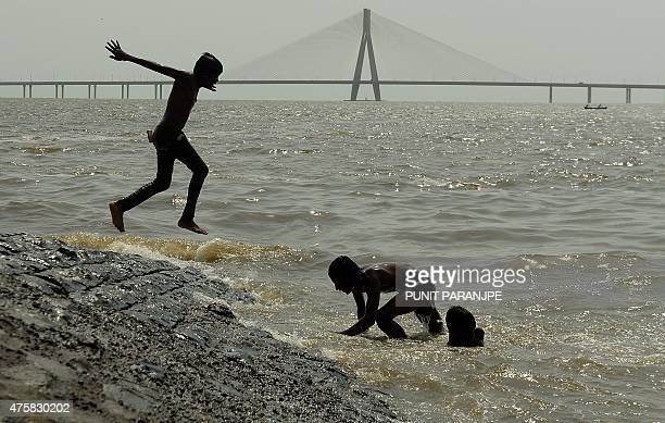 Indian children play in the sea against the background of the BandraWorli Sea Link cablestayed bridge on a hot afternoon in Mumbai on June 4 2015 AFP...