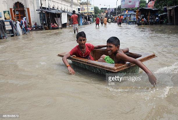 Indian children play on a flooded street in Kolkata on August 3 2015 Parts of the eastern city were flooded as the river Ganges burst its banks...