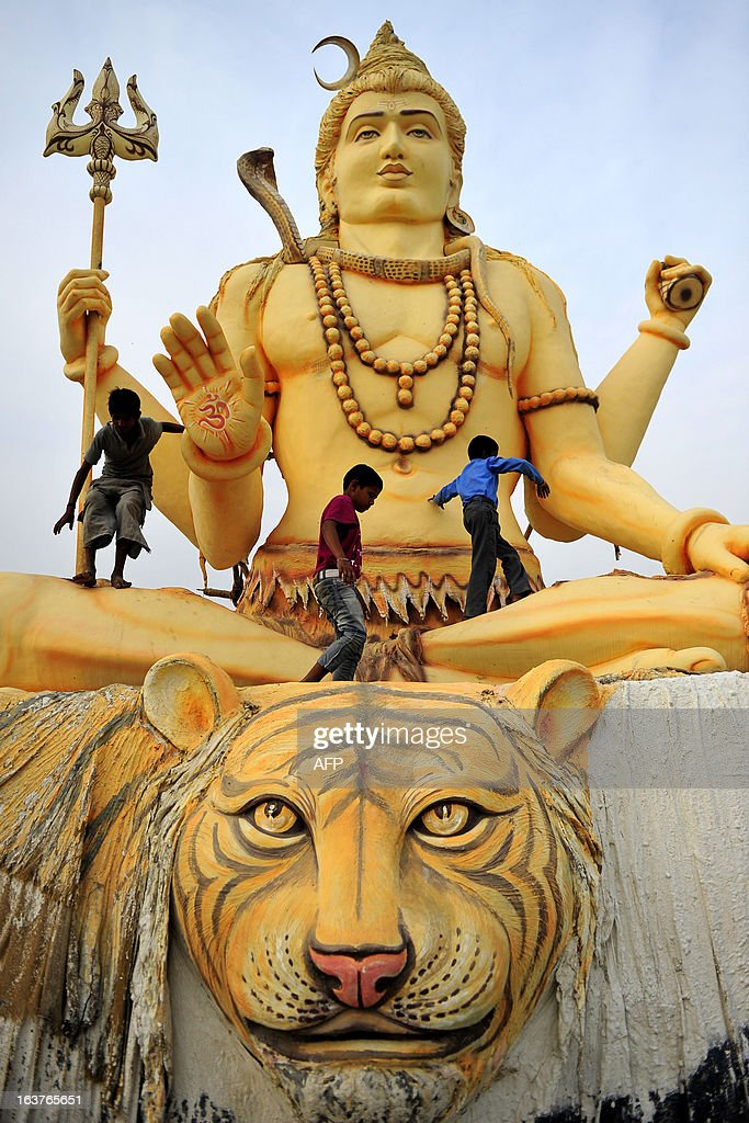 Indian children play on a giant statue of Hindu god Lord Shiva near the Sangam in Allahabad on March 15, 2013. The Sangam is a holy bathing site during The Kumbh Mela, which runs from January till March, and takes place every 12 years in Allahabad while smaller events are held every three years in other locations around India. AFP PHOTO/Sanjay KANOJIA