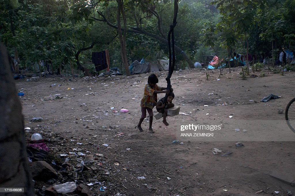 Indian children play on a swing near their makeshift shelters in a slum at the roadside in New Delhi on June 26, 2013, the International Day Against Drug Abuse and Illicit Trafficking. Activists in the city launched the 'Support Don't Punish' campaign calling for the removal of legal sanctions on low-level drug offenses and encouraging 'harm reduction' services such as needle exchange and opoid substitution therapy. AFP PHOTO/ Anna ZIEMINSKI