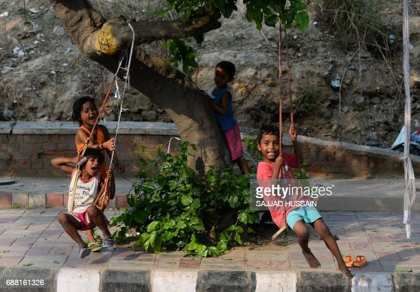 Indian children play on rope swings next to a road in New Delhi on May 25 2017 / AFP PHOTO / SAJJAD HUSSAIN