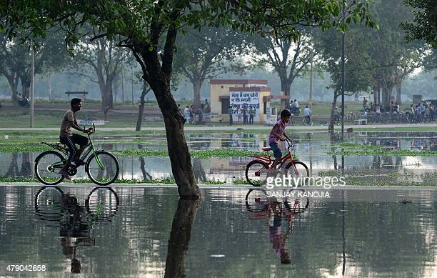 Indian children ride bicycles along a flooded pathway following heavy rain in Allahabad on June 30 2014 AFP PHOTO / SANJAY KANOJIA