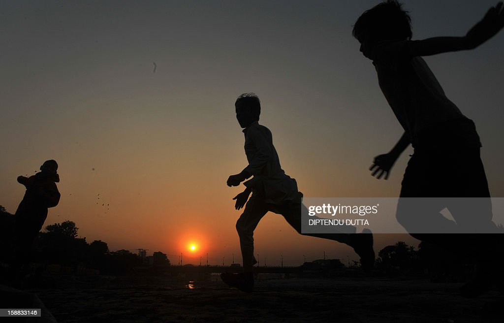 Indian children run through a field as the sunsets in Siliguri on December 31, 2012. Sydney will kick off a wave of dazzling firework displays welcoming in 2013, from Dubai to Moscow and London, with long-isolated Yangon joining the global pyrotechnics for the first time. AFP PHOTO/Diptendu DUTTA