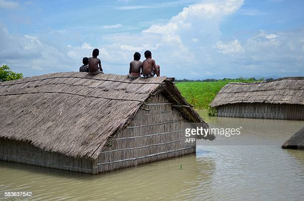 Indian children sit on the roof of a home submerged in flood waters in Batahidia on the Brahmaputra River in South Kamrup southwest of Guwahati on...