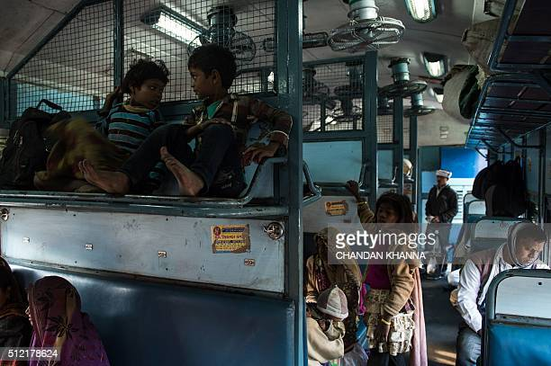 TOPSHOT Indian children sit on the top seat of the wagon as they wait for a train to leave Hazrat Nizamuddin railway station in New Delhi on February...