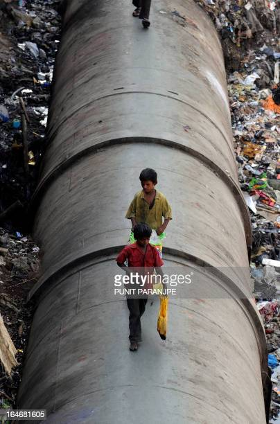 Indian children walk along a water pipeline in the Dharavi slum of Mumbai on April 20 2010 April 22 marks the 40th Earth Day which urges local action...