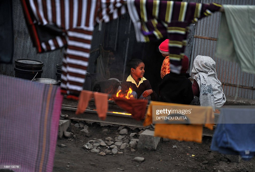 Indian children warm themselves around a bonfire at a slum during a foggy and cold day in Siliguri on January 8, 2013. As thousands of homeless people sought places in temporary shelters, the unusual cold in throughout India has been attributed to dense fog which has obscured the sun and disrupted airports and trains, as well as icy winds from the snowy Himalayas to the north. AFP PHOTO/Diptendu DUTTA