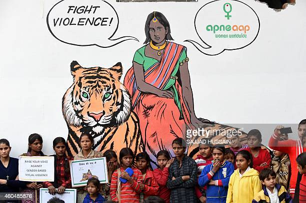 Indian children watch a play by activists in front of a mural depicting fictional character Priya who is a rape survivor sitting on a tiger before a...